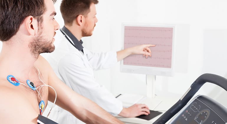 Cardiologist Technologist explaining Stress Testing results for patient on a treadmill.