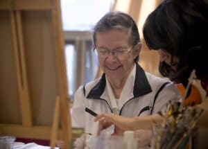 A Therapeutic Recreation Assistant helps a resident during art class.
